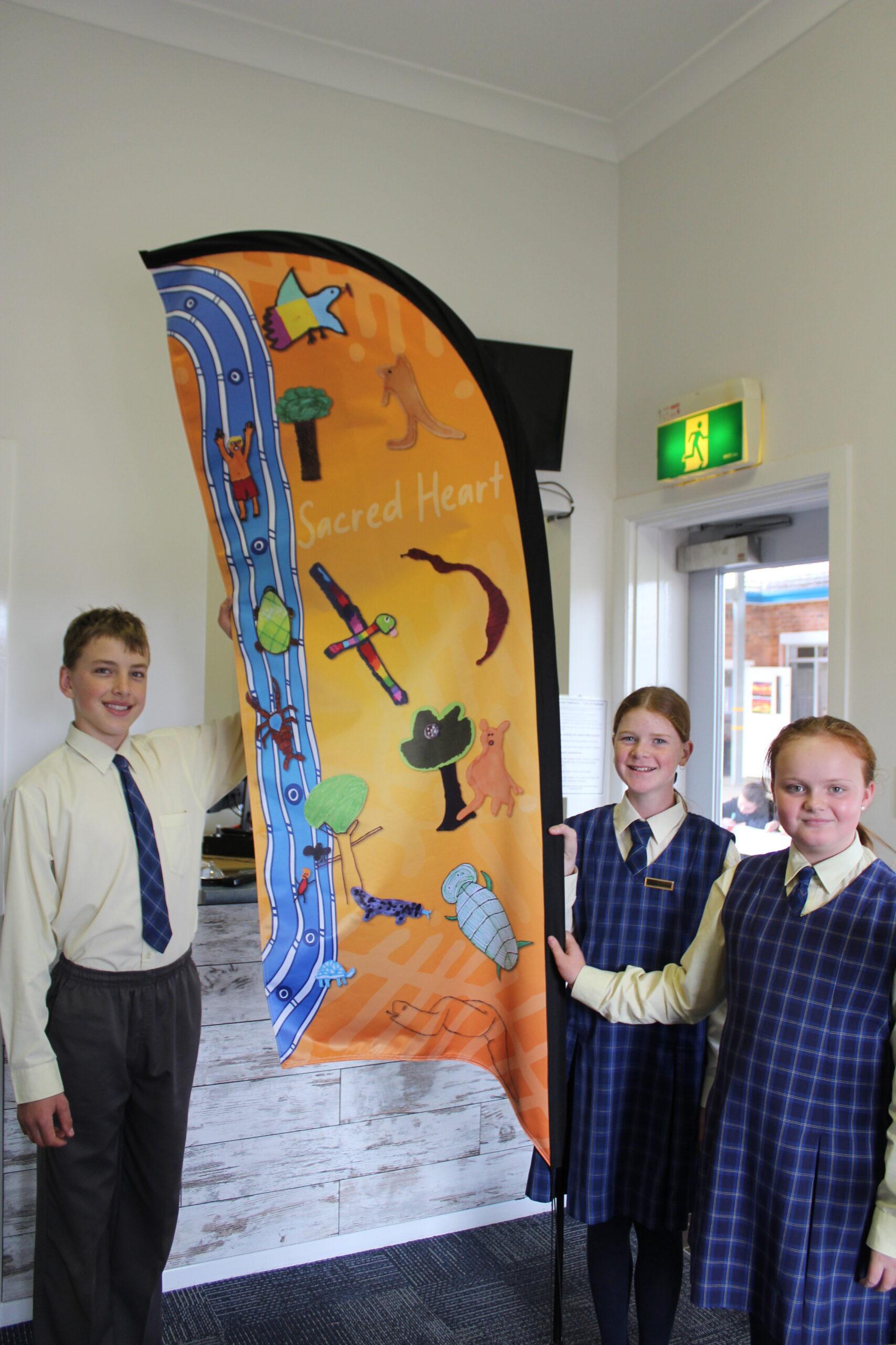 Proudly displaying their school banner, Jack Rees, Hallie Thomson and Tori Whelan.